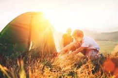 Le père apprennent sa tente de camping d'installation de fils sur la clairière de forêt de coucher du soleil photos libres de droits