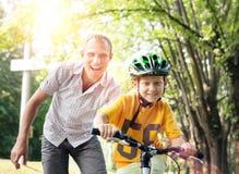Le père apprennent son fils pour monter la bicyclette photo libre de droits