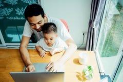 Le père asiatique et son fils utilise l'ordinateur portable images libres de droits