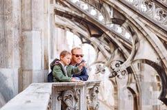 Le père avec des touristes de fils sont sur le toit de Milan Cathedral Photographie stock
