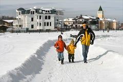 Le père avec deux garçons marchent sur le journal de neige Photographie stock libre de droits