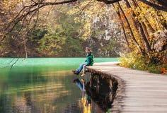 Le père avec le fils s'asseyent sur le pont près du lac de montagne, le soleil d'automne Photos stock