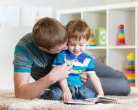 Le père avec le fils d'enfant a lu le livre d'enfants photo stock
