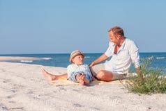 Le père avec le fils prennent un bain du soleil sur la plage de mer photos stock