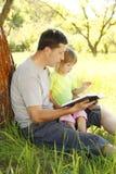 Le père avec sa petite fille lit la bible Photographie stock libre de droits