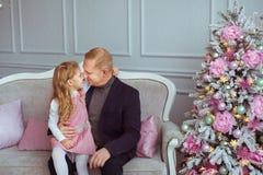 Le père avec sa petite fille s'asseyent sur le sofa près de l'arbre de Noël Photographie stock libre de droits
