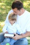 Le père avec un jeune descendant a affiché la bible en nature image libre de droits