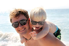 Le père Carrying Happy Child ferroutent dessus sur la plage par l'océan Images libres de droits