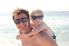 Le père Carrying Son ferroutent dessus sur la plage par l'océan Photo libre de droits