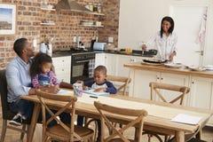 Le père And Children Drawing au Tableau comme mère prépare le repas photos libres de droits