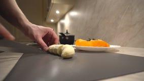 Le père coupe la banane pour ses enfants pour le casse-croûte d'après-midi clips vidéos