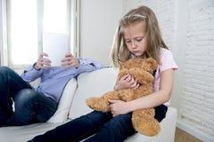 Le père d'intoxiqué d'Internet à l'aide de la protection numérique de comprimé ignorant la petite fille triste a ennuyé étreindre Photo stock