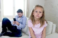 Le père d'intoxiqué d'Internet à l'aide du téléphone portable ignorant la petite fille triste a ennuyé seul et déprimé photographie stock