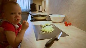 Le père dans une chemise rayée fait cuire la salade végétale organique fraîche, consommation saine pour des enfants clips vidéos
