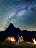 Le père de famille de touristes et la femme regardant brille le ciel étoilé la nuit Randonneurs de couples s'asseyant près du cam Images stock