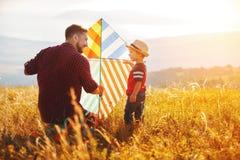 Le père de famille et le fils heureux d'enfant lancent le cerf-volant sur le pré Photos libres de droits