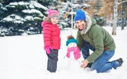 Le père de famille et la fille heureux d'enfant fait le bonhomme de neige en hiver Photographie stock