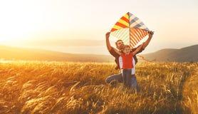 Le père de famille et la fille heureux de bébé lancent le cerf-volant sur le pré Image stock