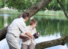 Le père demande à des articles de pêche de fils trop pour pêcher Photos libres de droits