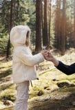 Le père donne un crocus de fleur à sa petite fille Le père et la fille sur une montagne marchent, forêt de pin avec des wildflowe photographie stock libre de droits