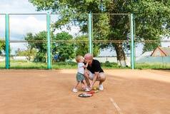 Le père embrasse la fille avant jouer dans le tennis photo stock