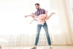 Le père enseigne à danser sa petite fille mignonne images stock