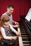 Le père enseigne la jeune fille jouant le piano Images libres de droits