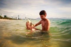 le père enseigne la petite fille à nager en eau de mer peu profonde Image libre de droits