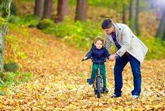 Le père enseigne le fils à monter la bicyclette Photographie stock libre de droits