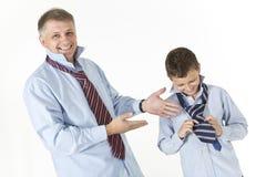 Le père enseigne son fils à attacher un noeud sur un lien Image stock
