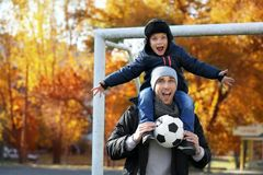 Le père et le fils avec la boule sur le football lancent images libres de droits