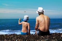 Le père et le fils dans des troncs de natation s'asseyent par le ressac photo libre de droits