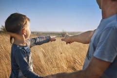 Le père et le fils dans le domaine au coucher du soleil, doigts de point à l'horizon, regardent loin, famille, émotions, photo mo Photos stock