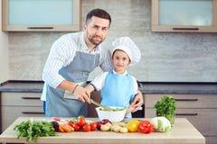Le père et le fils font cuire dans la cuisine photos libres de droits