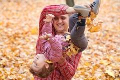 Le père et le fils jouent et ont l'amusement en parc de ville d'automne Ils posant, sourire, jouant Arbres jaunes lumineux images stock