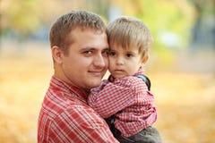 Le père et le fils jouent et ont l'amusement en parc de ville d'automne Ils posant, sourire, jouant Arbres jaunes lumineux photos stock