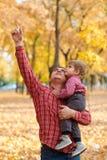 Le père et le fils jouent et ont l'amusement en parc de ville d'automne Ils posant, sourire, jouant Arbres jaunes lumineux photo libre de droits