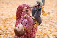 Le père et le fils jouent et ont l'amusement en parc de ville d'automne Ils posant, sourire, jouant Arbres jaunes lumineux photographie stock libre de droits