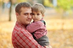 Le père et le fils jouent et ont l'amusement en parc de ville d'automne Ils posant, sourire, jouant Arbres jaunes lumineux photos libres de droits