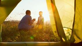 Le père et le fils jouent près de la tente de touristes sur le coucher du soleil Photographie stock libre de droits