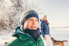 Le père et le fils marchent avec le chien dans la forêt de neige au jour d'hiver ensoleillé Photographie stock libre de droits