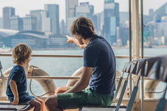 Le père et le fils nagent en le ferry par le port de Victoria en Hong Kon Photo stock