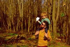 Le père et le fils ont plaisir à marcher au printemps le parc Le père et l'enfant apprécient le jour ensoleillé extérieur L'amour photos libres de droits