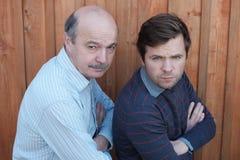 Le père et le fils se sont disputés Ils regardent avec émotion fâchée l'appareil-photo, bras croisés image stock