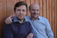Le père et le fils se tiennent ensemble près du fond en bois Photo stock