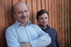 Le père et le fils se tiennent ensemble près du fond en bois Photo libre de droits