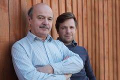 Le père et le fils se tiennent ensemble près du fond en bois Photos libres de droits