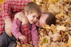 Le père et le fils se trouvent sur les feuilles jaunes et ont l'amusement en parc de ville d'automne Ils posant, sourire, jouant  photos stock