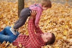 Le père et le fils se trouvent sur les feuilles jaunes et ont l'amusement en parc de ville d'automne Ils posant, sourire, jouant  images stock