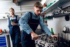 Le père et le fils travaillent au service automatique Deux mécaniques travaillent avec les détails de la voiture photographie stock libre de droits